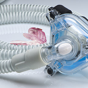 Oral appliance and CPAP mask resting together on table
